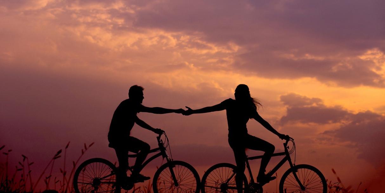 Coppia in bicicletta al tramonto